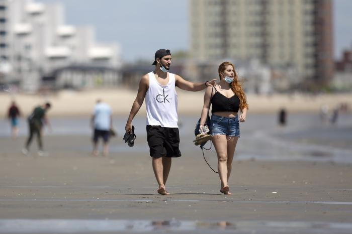 A couple walks on Revere Beach, Saturday, May 16, 2020, in Revere, Mass. (AP Photo/Michael Dwyer)