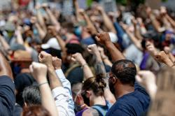 In this Saturday, May 30, 2020, file photo, demonstrators raise fists in the air during a march in Pittsburgh to protest the death of George Floyd, who died after being restrained by Minneapolis police officers on May 25