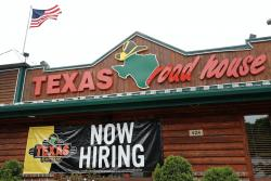 "A ""Now Hiring"" sign Is displayed outside a Texas Roadhouse restaurant, Friday, June 5, 2020, in Methuen, Mass."