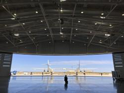 In this Aug. 15, 2019 file photo, Virgin Galactic ground crew guide the company's carrier plane into the hangar at Spaceport America following a test flight over the desert near Upham, New Mexico