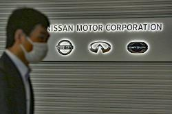 A man walks past the corporate logos at the global headquarters of Nissan Motor Co., Ltd. in Yokohama near Tokyo, Thursday, May 21, 2020