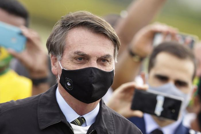 In this May 25, 2020, file photo, Brazil's President Jair Bolsonaro, wearing a face mask amid the coronavirus pandemic, stands among supporters as he leaves his official residence of Alvorada palace in Brasilia, Brazil