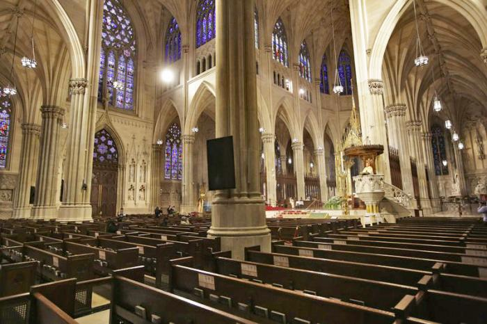 In this Sunday, April 12, 2020 file photo, Archbishop Timothy Dolan, right, delivers his homily over mostly empty pews as he leads an Easter Mass at St. Patrick's Cathedral in New York