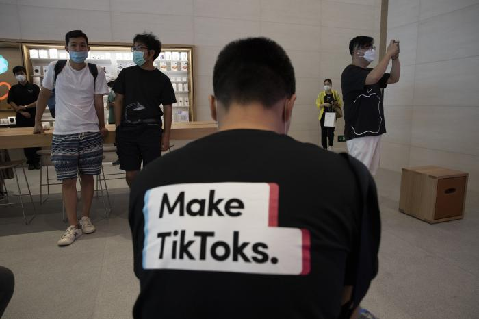A man wearing a shirt promoting TikTok is seen at an Apple store in Beijing.