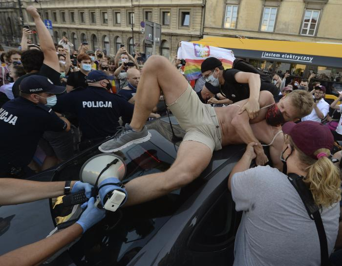 An activist climbs onto a police car to protest the detention of an LGBT activist in Warsaw, Poland.