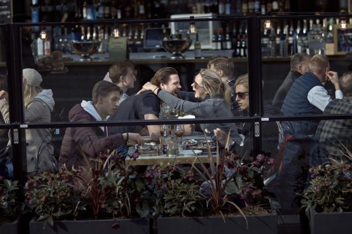 In this Saturday, April 4, 2020 file photo a couple hug and laugh as they have lunch in a restaurant in Stockholm, Sweden.