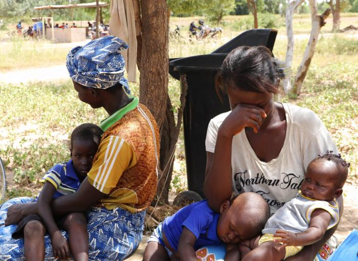 Two women sit outside a small clinic in Gampela village on the outskirts of Burkina Faso's capital, Ouagadougou