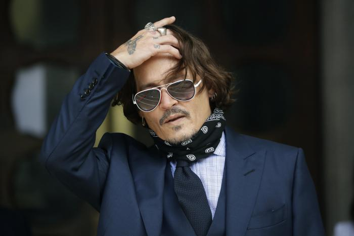 Johnny Depp gestures to the media as he arrives at the High Court in London.