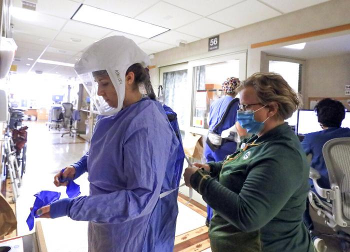 Deb Dalsing, nurse manager of the COVID-19 treatment unit at UW Health assists nurse Ainsley Billesbach with her personal protective equipment at the hospital in Madison, Wis.