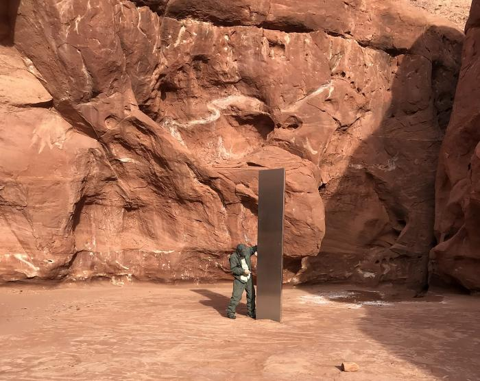A Utah state worker inspecting a metal monolith that was found installed in the ground in a remote area of red rock in Utah.