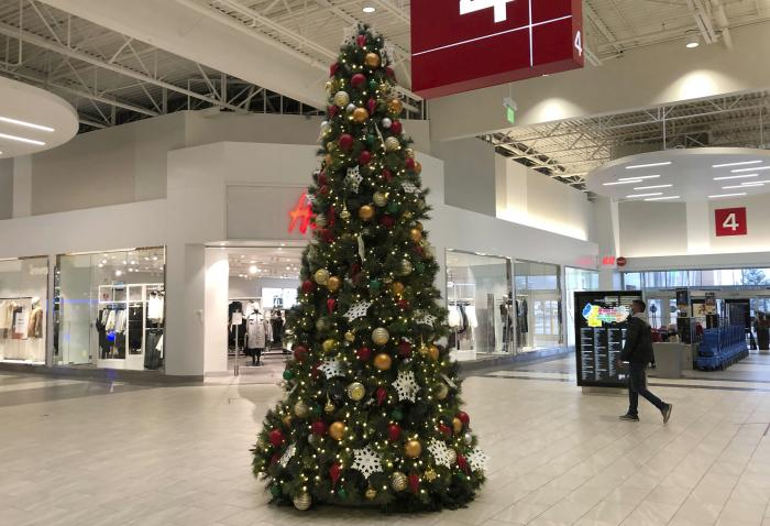 A lone shopper walks past the Christmas tree set up in an outlet mall Monday, Nov. 9, 2020, in Lakewood, Colo.