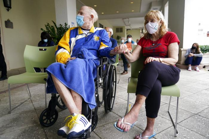 Residents Ken Fishman, 81, left, and Esther Wallach, 82, hold hands as they wait in line for the Pfizer-BioNTech COVID-19 vaccine at the The Palace assisted living facility in Coral Gables, Fl.