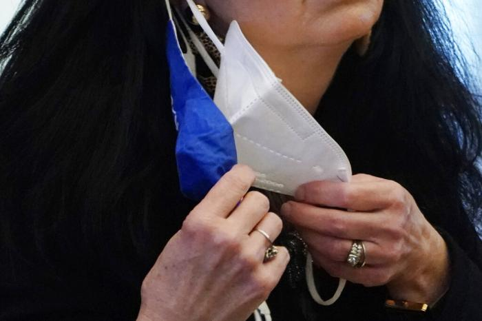 A state legislator adjusts her face masks while asking a question at the Capitol in Jackson, Miss.