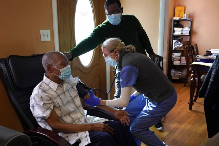 Edouard Joseph, 91, left, has his blood pressure taken by geriatrician Megan Young, right, as Joseph's son, Edouard F. Joseph, top, offers support after his father received a COVID-19 vaccination.
