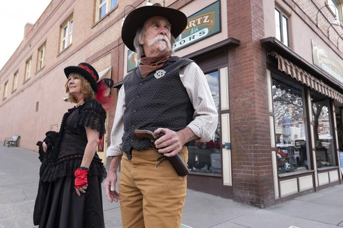 Old West actors Cathy Roberts and Scott Perez stand on the lookout for unmasked visitors in Durango, Colorado.