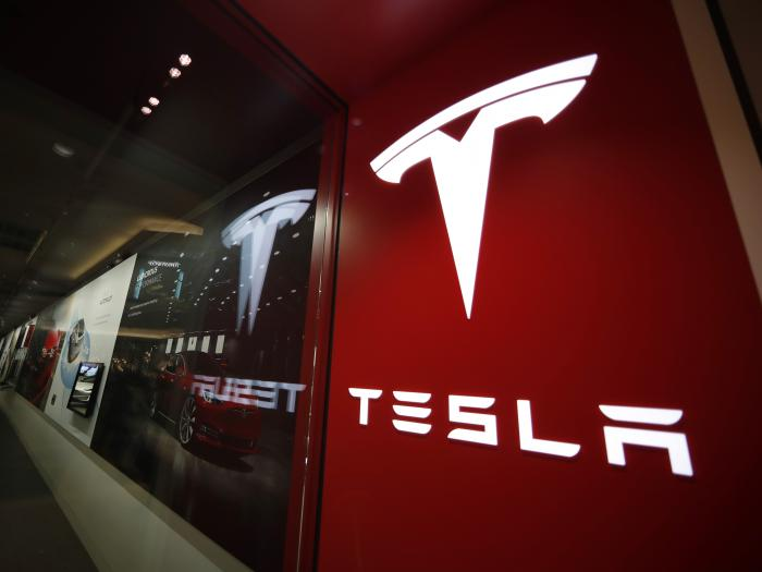This Feb. 9, 2019, file photo shows a sign bearing the company logo outside a Tesla store in Cherry Creek Mall in Denver
