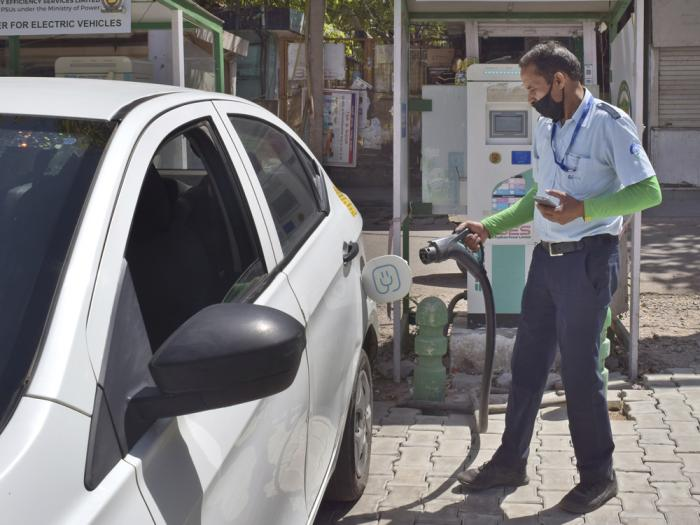 A driver of an electric car charges his vehicle at public charging station in New Delhi, India, Thursday, April 1, 2021