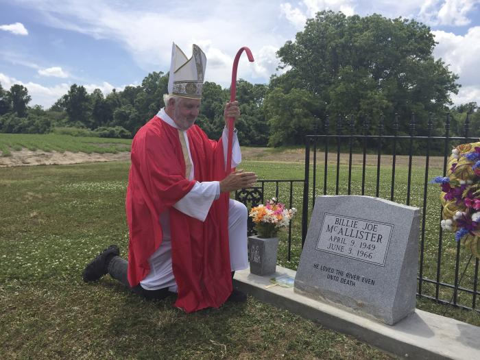 """Bill Luckett of Clarksdale, appearing as a pope, kneels beside the monument for the fictional Billy Joe McAllister made famous by former Greenwood resident, Bobbie Gentry's song """"Ode to Billy Joe,"""" at Tallahatchie Flats near Greenwood, Miss.,"""