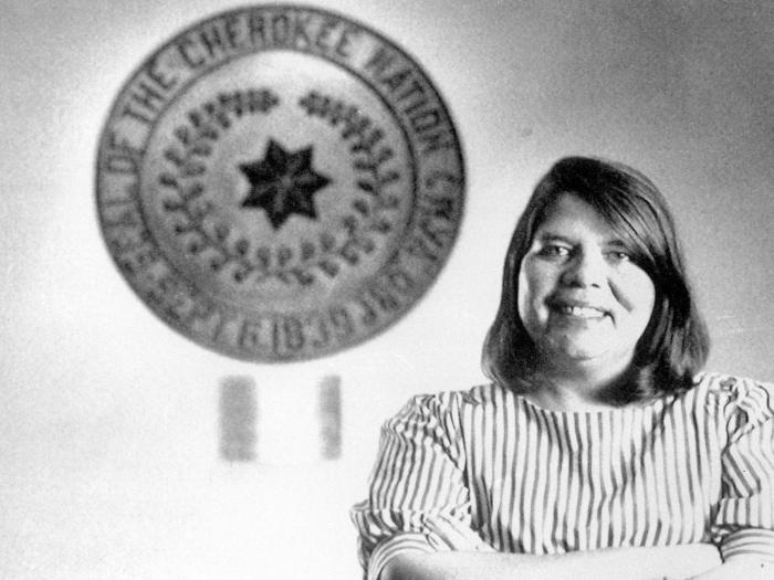 In this July 19, 1985, file photo, Wilma Mankiller, the first woman elected chief of the Cherokee Nation, poses in front of the tribal emblem at the Cherokee Nation in Oklahoma