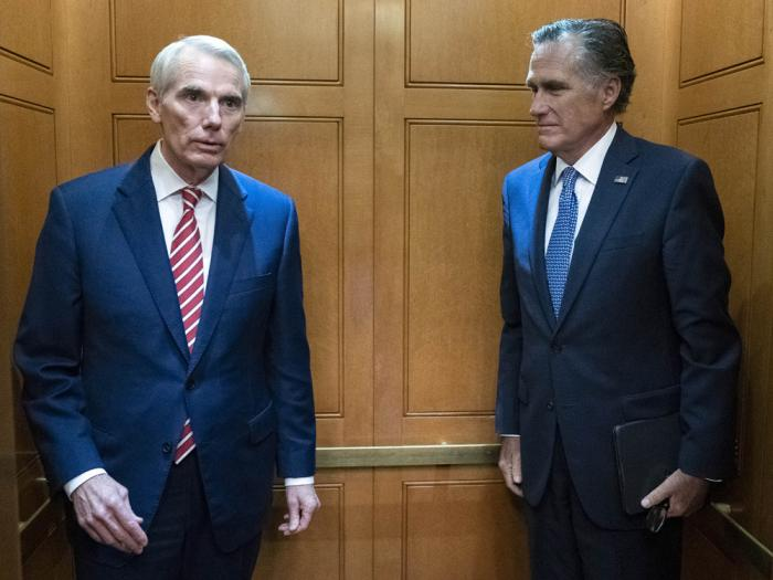 Sen. Rob Portman, R-Ohio, left, accompanied by Sen. Mitt Romney, R-Utah, leave in the elevator after a closed door talks about infrastructure on Capitol Hill in Washington Thursday, July 15, 2021
